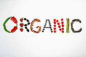 The word Organic spelled from peppers, strawberries, blackberries, almonds, blueberries, raspberries, asparagus, and pumpkin seeds on a white background, Calgary, Alberta, Canada