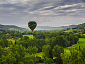 A hot air balloon flies low over a spring valley landscape, Tuscany, Italy