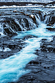 Turquoise water flowing over rocks into a river, Bruarfoss, Iceland