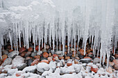 Icicles and snow over pebbles on the shore of Lake Superior