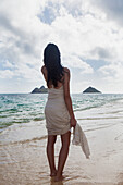 Young woman in white dress on the beach at the water's edge, Kailua, Island of Hawaii, Hawaii, United States of America
