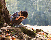 Young boy in a contemplative mood in a forest under an oak tree in a rainforest, Langley, British Columbia, Canada