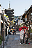 Young Japanese couple in kimono posing under a red umbrella in a narrow street with pagoda in the distance, Kyoto, Japan