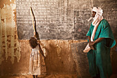 Tuareg teacher and girl in front of a blackboard at a primary school in Tiriken, Mali