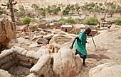 Senior man walking by the Toguna House of words in Tireli, Mali