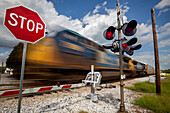 Train with blurred movement passing from right to left at a railroad crossing that has the safety gate down, stop sign, and flashing lights, United States of America
