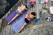 Women practicing yoga on wooden dock