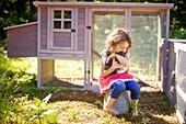 Girl hugging chicken in farm yard