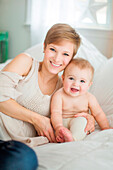 Caucasian mother and baby daughter smiling on bed
