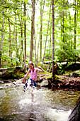 Caucasian girl splashing in river