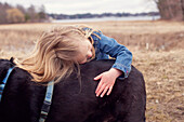 Close up of girl hugging dog in rural field