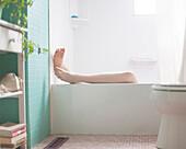 Legs of Caucasian woman relaxing in bath