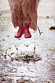Caucasian girl in rain boots jumping in rain puddles