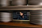 Working chef viewed through stacks of plates in restaurant kitchen