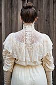 Caucasian woman wearing vintage gown near wooden fence