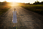 Caucasian girl walking on dirt road