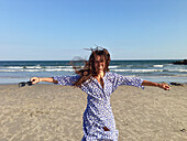 Smiling woman with arms outstretched on beach
