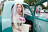 Bride blowing a kiss from vintage truck