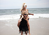 Woman carrying friend piggyback on beach