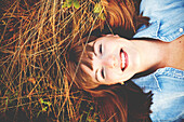 Close up of smiling woman laying in tall grass