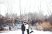 Couple kissing in snowy rural field