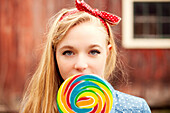 Caucasian teenage girl licking lollipop