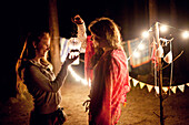 Girls holding lantern at campsite at night