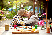 Couple kissing at picnic table in forest