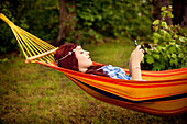 Girl using cell phone and laying in hammock
