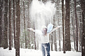 Girl playing in snowy forest