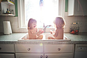 Twin girls bathing in kitchen sink