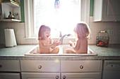 Twin girls bathing in kitchen sink