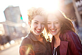 Women hugging on sunny city sidewalk