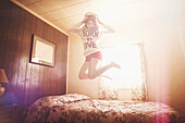 Caucasian girl in captain hat jumping on bed