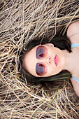 Caucasian woman laying in hay