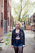 Caucasian teenage girl standing on city sidewalk
