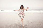 Caucasian woman running in waves on beach