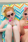 Caucasian girls sunbathing and drinking soda