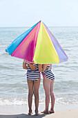 Caucasian girls under umbrella on beach