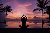 Silhouette of woman meditating near swimming pool at sunset