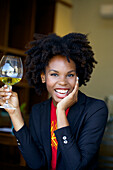 Smiling woman drinking glass of white wine