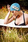 Woman wearing vintage swim cap in bathtub in backyard