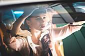 Glamorous mixed race woman checking hair in car mirror
