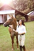 Equestrian woman walking horse in yard