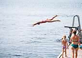 Caucasian girl jumping from diving board into lake