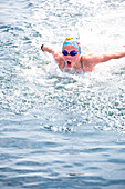 Caucasian swimmer gasping for air in lake