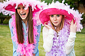 Caucasian teenage girls wearing feather boas and hats