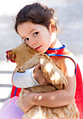 Mixed race girl hugging chicken