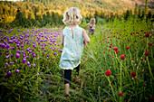 Girl walking in rural field of flowers