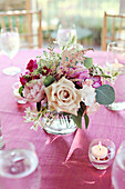 Bouquet of flowers in vase on pink tablecloth